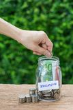 Woman hand putting coin in glass jar bottle labeled as Education stock images