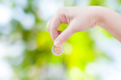 Woman hand putting a coin on green nature background,saving Stock Photos