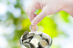 Woman hand putting a coin on green nature background,saving Royalty Free Stock Photos