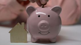 Woman hand putting coin in piggybank near little wooden house, charity donation. Stock footage stock video footage