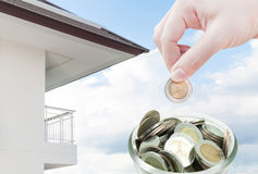 Woman hand putting a coin on ,saving ,Donation Investment ,Coins in hands money Savings and apartment Stock Photos