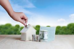 Woman hand putting the coin in to wooden house piggy bank financial metaphor saving money for buy home concept on wooden table. And wood background royalty free stock photos