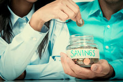 Woman hand putting money coin in the glass jar labeled SAVINGS Royalty Free Stock Images