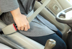 Woman hand putting on safety belt Stock Images
