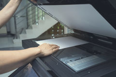 Woman hand putting a sheet of paper into a copying device. Close up Stock Images