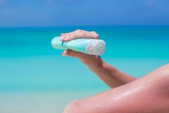 Woman hand putting sunscreen from a suncream Stock Photo