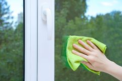 A woman hand with a rag washes the window glass. stock image
