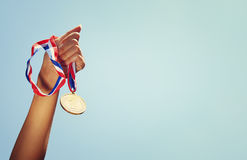 Woman hand raised, holding gold medal against sky. award and victory concept.  Royalty Free Stock Image