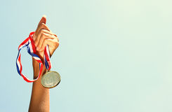 Woman hand raised, holding gold medal against sky. award and victory concept Royalty Free Stock Photography