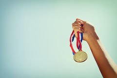 Woman hand raised, holding gold medal against sky. award and victory concept.  stock photo