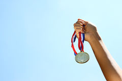 Woman hand raised, holding gold medal against sky. award and victory concept.  Royalty Free Stock Photos