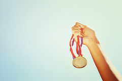 Woman hand raised, holding gold medal against sky. award and victory concept.  Royalty Free Stock Images