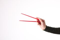 Woman hand with red chopsticks Royalty Free Stock Photos