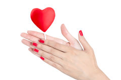 Woman hand with red nails holding heart Lollipop. Stock Image