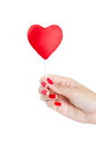 Woman hand with red nails holding heart Lollipop. Stock Photo
