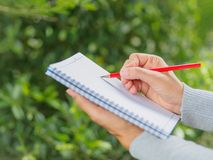 Woman hand with red pencil writing on notebook. In agriculture garden stock image