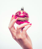 Woman hand with red pink New Year toy and manicure on white Royalty Free Stock Photos
