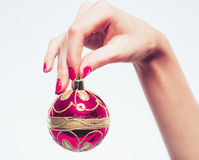 Woman hand with red pink New Year toy and manicure on white Stock Images