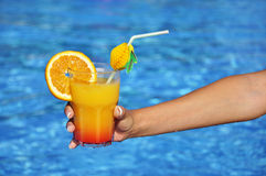 Woman hand with refreshment at swimming pool Royalty Free Stock Photography