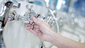 Woman hand rotates the polished aluminum valve of water tap in bath.  stock video