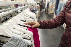 Woman hand rummaging in the clothing store, consumerism concept. Royalty Free Stock Photo