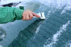 Woman hand scraping snow and ice from car windows. Stock Photos