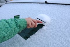 Woman hand scraping snow and ice from car windows. Stock Photo