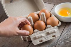 Woman hand selected egg in egg carton and yolk in bowl Stock Images