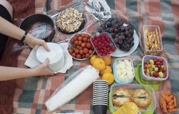 Woman hand serving cake on picnic table with food served outdoors on the fabric picnic cloth. Close up, top view. Fresh royalty free stock photography