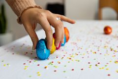 Woman hand setting up colorful chocolate easter eggs royalty free stock photo