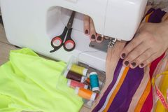 Woman hand on sewing machine.Dressmaker work on the sewing machine. Hobby sewing fabric as a small business concept Royalty Free Stock Images