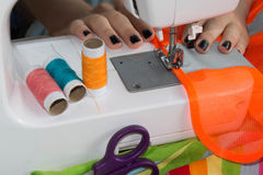 Woman hand on sewing machine.Dressmaker work on the sewing machine. Hobby sewing fabric as a small business concept Royalty Free Stock Image