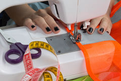 Woman hand on sewing machine.Dressmaker work on the sewing machine. Hobby sewing fabric as a small business concept. Female thread Stock Photos