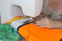 Woman hand on sewing machine.Dressmaker work on the sewing machine. Hobby sewing fabric as a small business concept Royalty Free Stock Photography