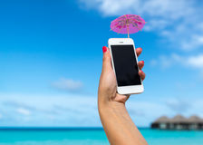 Woman hand showing a blank smart phone on the beach Stock Photo