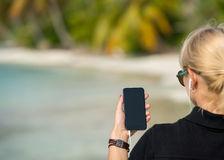 Woman hand showing a blank smart phone on the beach with the sea Stock Photos