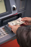 Woman hand showing dollar banknotes in front of the atm Royalty Free Stock Photography
