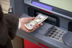 Woman hand showing dollar banknotes in front of the atm Stock Images