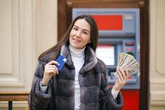 Woman hand showing dollar banknotes in front of the atm Royalty Free Stock Photo