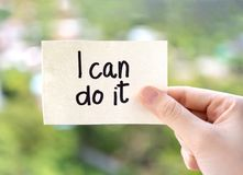Woman hand showing I can do it texts on paper note on green nature background. Positive attitude, self belief and motivation. Concept royalty free stock images