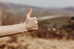 woman hand showing like with thumb up on background of sunny mountains, approval and travel concept royalty free stock photography