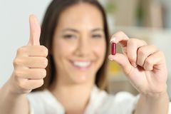 Woman hand showing a medicine capsule with thumbs up stock photos