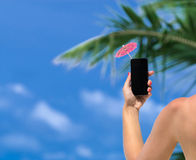 Woman hand showing mobile phone and cocktail umbrella Stock Images