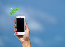 Woman hand showing mobile phone and cocktail umbrella on the sky Stock Images
