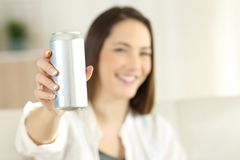Woman showing a soda refreshment can. Woman hand showing a soda refreshment can sitting on a couch in the living room at home royalty free stock images