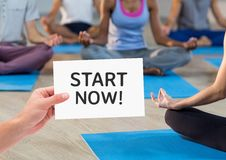 Woman hand showing start now text written on page in fitness studio Stock Photo
