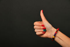 Woman hand shows thumb up gesture over black. Woman hand with manicure nails and colorful wooden painted beads bracelet shows ok thumb up like gesture sign over Stock Photography