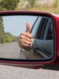 Woman hand with the sign of peace in the view mirror focus mirr Royalty Free Stock Image