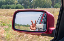 Woman hand with the sign of peace in the view mirror focus mirr Royalty Free Stock Images