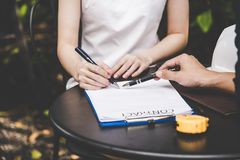 Woman hand signing a contract for building house with architect man. Stock Photography
